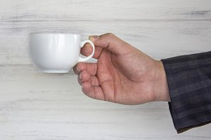 cup in the businessman's hand.