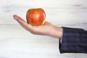 red apple in the businessman's hand.