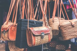 Rattan handbags hanging in the outdoor local asian store. Bali island.