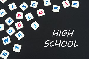English colored square letters scattered on black background with text high school
