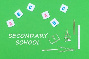 From above wooden minitures school supplies and ABC letters on green background with text secondary school