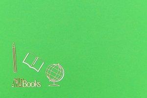 School supplies wooden miniatures on green background