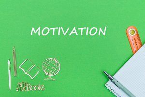School supplies wooden miniatures and notebook with text motivation on green background