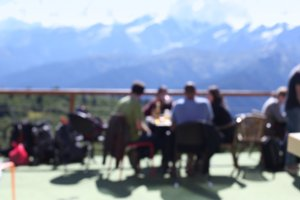Terrace with people. Mountain views.