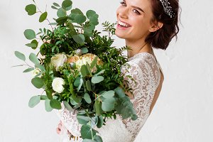 Happy bride laughing with a bouquet