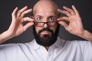 Portrait of bald unshaven man holding glasses on dark background