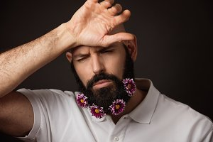 Portrait of tired unshaven man with beard and moustache with chrysanthemum flowers