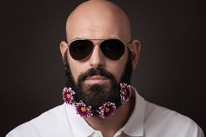 Unshaven man with beard and moustache with chrysanthemum flowers and sunglasses on dark background