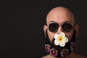 unshaven man with beard with flowers and sunglasses on dark background with copyspace