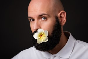 Portrait of unshaven man with beard with flower