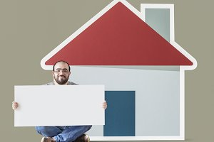 Man holding poster with house mockup