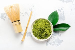 Green matcha tea powder and tea accessories on white background