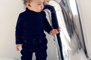 baby boy in black clothes one year with silver