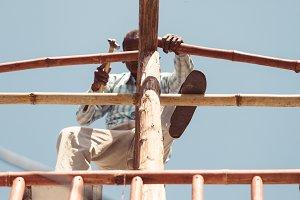 indian man repairing the roof