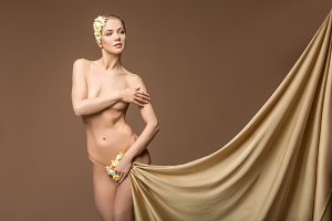 beautiful naked woman with flowers between legs  and silk fabrics