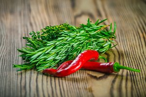 Bunches of fresh herbs thyme, salad and rosemary, red chili peppers on wooden board