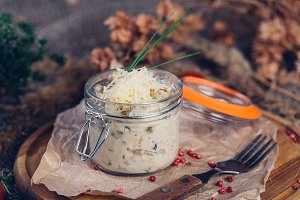 Julienne with chicken and mushrooms in a glass serving jar sprinkled with Parmesan cheese