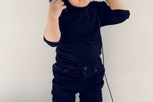 one-year-old baby in black clothes listening to rock music