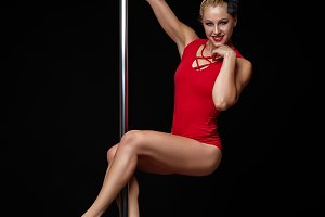 beautiful pole dancer in red bodywear on pylon