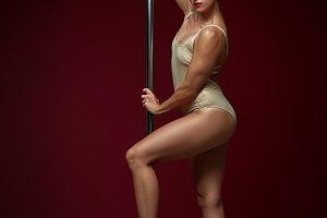 beautiful pole dancer in golden bodywear on pylon