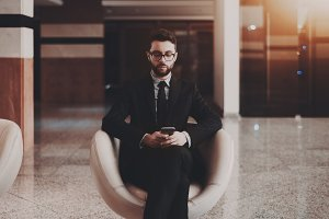 Businessman indoors, with smartphone