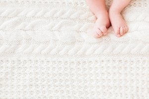 Baby feet, white knitted background