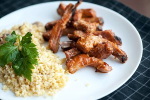 grilled pork with rib in white dish, served with bulgur