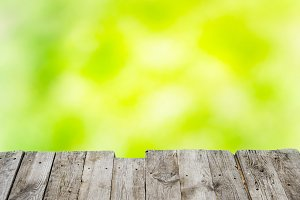 Wooden table over green background