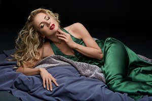 beautiful blond girl lying in green dress