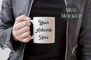 Woman holding mug- leather jacket