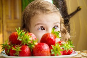 Child and strawberry.