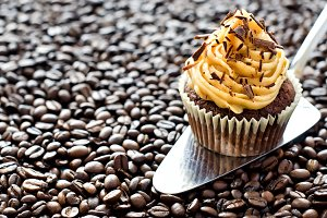 Cupcake on brown coffee background