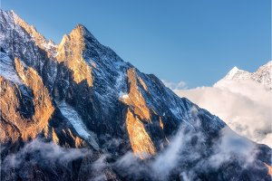 Mountains with sunlit peaks in clouds in Nepal