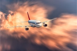 Airplane with motion blur effect is flying in big orange clouds