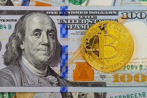 Gold Bitcoin on hundred dollars bill