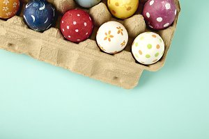 Coloeful easter eggs in nest on pastel blue color background with space