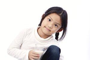 Cute little asian girl drinking fresh organic milk healthy nutrition for small children