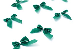 Green velvet bows on white background