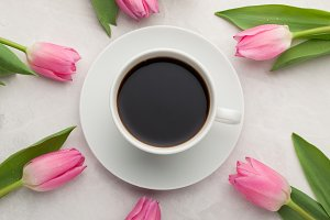 Black coffee in white Cup with pink tulips on light stone background. Top view