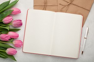 Blank note pad with pen, envelopes and pink tulips on light stone background