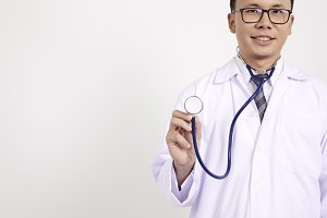 Portrait of a friendly handsome asian male doctor dressed in uniform holding stethoscope