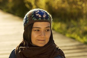 woman on footpath with hat and scarf