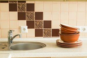 Dishes in the sink with kitchen background