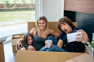 Family making selfie sitting inside moving box