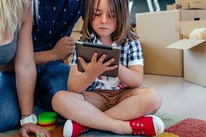 Parents supervising their little son playing tablet