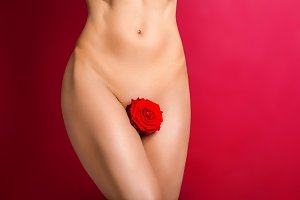 beautiful woman naked body with flower between legs