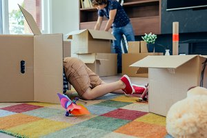 Boy playing inside a moving box while his father unpacks