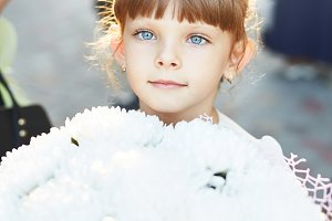 little girl with a big bouquet of flowers