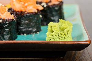 Wasabi with baked sushi rolls on turquoise plate