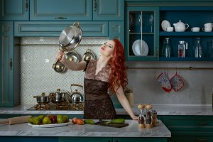 Red-haired woman holds a frying pan.